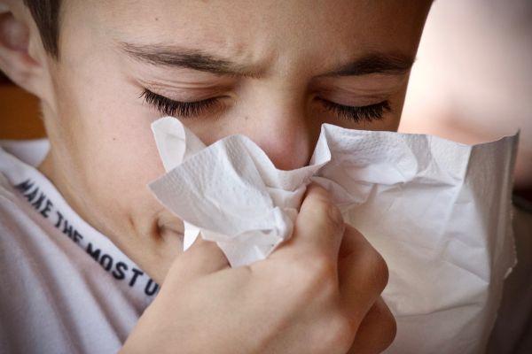 Bambino si soffia il naso in un fazzoletto
