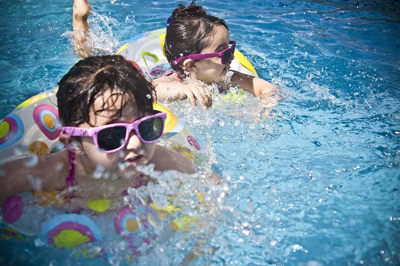 Bambine con occhiali da sole nuotano in piscina aiutate dalle ciambelle