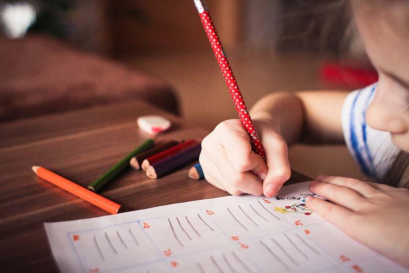 Bambino fa i compiti con la matita