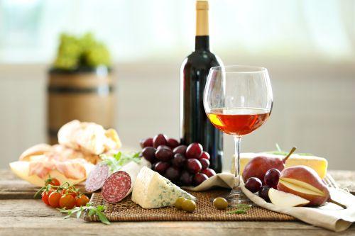 Calice di vino con tagliere di salumi, formaggi e frutta