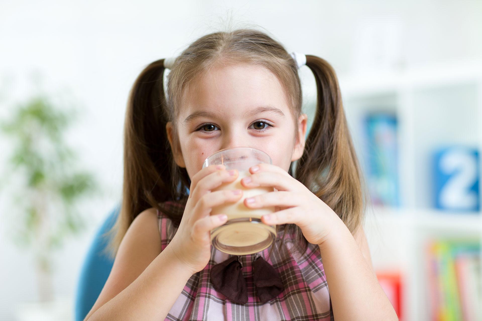 Bambina che beve un bicchiere di latte